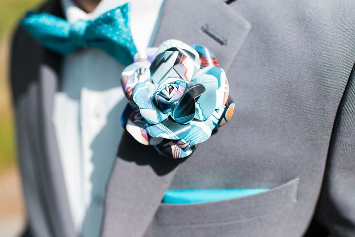"Dave chose a slim gray suit with an ivory shirt and a turquoise bow tie to reflect their wedding color. Jess made his boutonniere from the comics of one of his favorite movies, ""Back to the Future."""