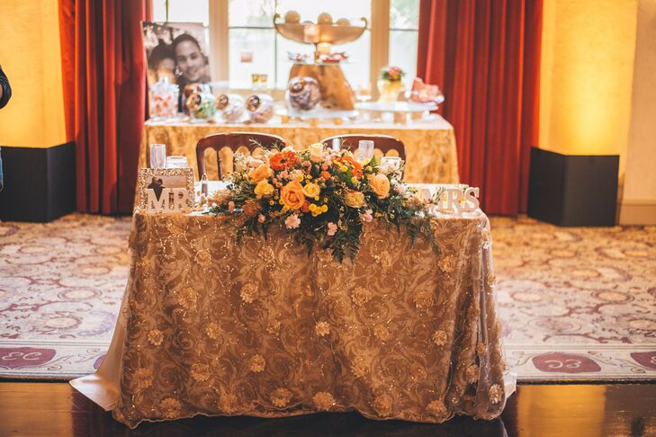 """The gold sweetheart table was decorated with a flower arrangement of dahlias, gerbera daisies and roses accented with fern. A """"Mr"""" and """"Mrs"""" sign decorated the table as well."""