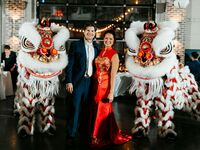 Bride and groom with traditional Asian lion dancers at wedding reception