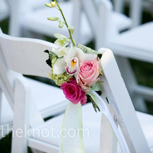 Petite arrangements of roses and orchids decorated the aisle chairs at the ceremony.