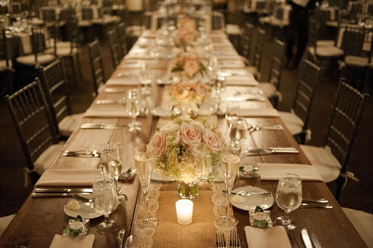 The long head table was covered with a lace-trim burlap runner and decorated with low centerpieces made up of pink roses, white hydrangeas and waxflowers.