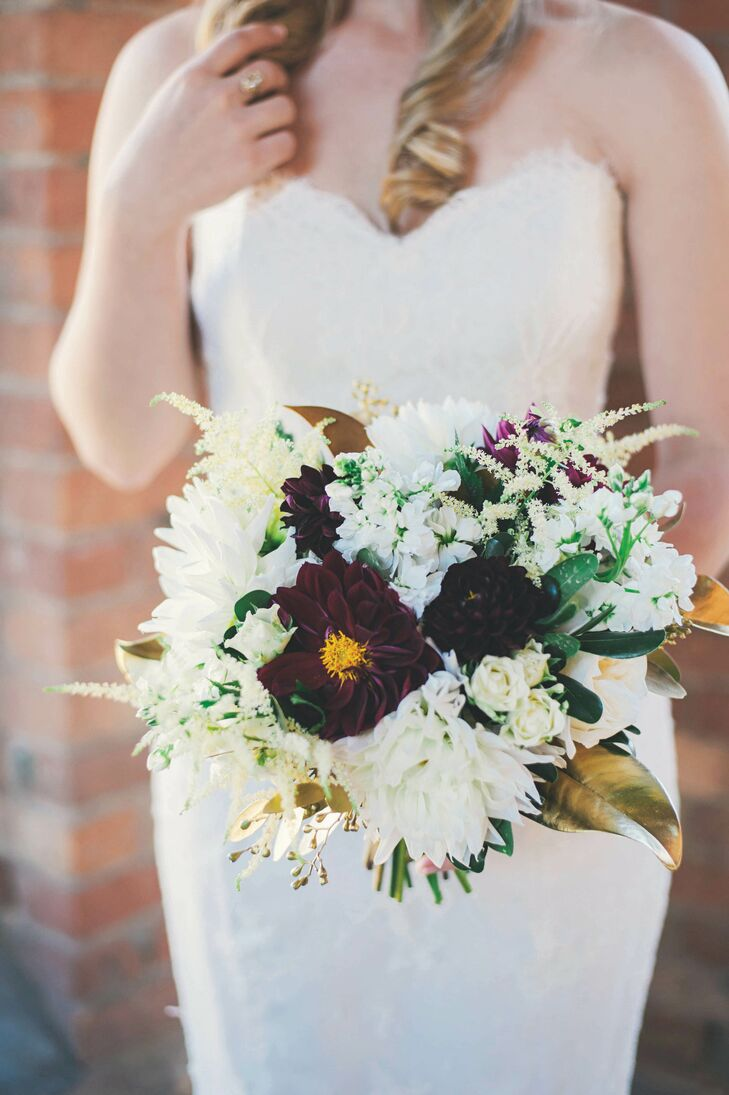 """Laura carried a gilded bunch of white garden roses, astilbes, spray roses, burgundy dahlias and dark green foliage complete with gold-dipped magnolia leaves. """"I wanted to tie in a darker flower to complement the black bridesmaid dresses,"""" she says."""