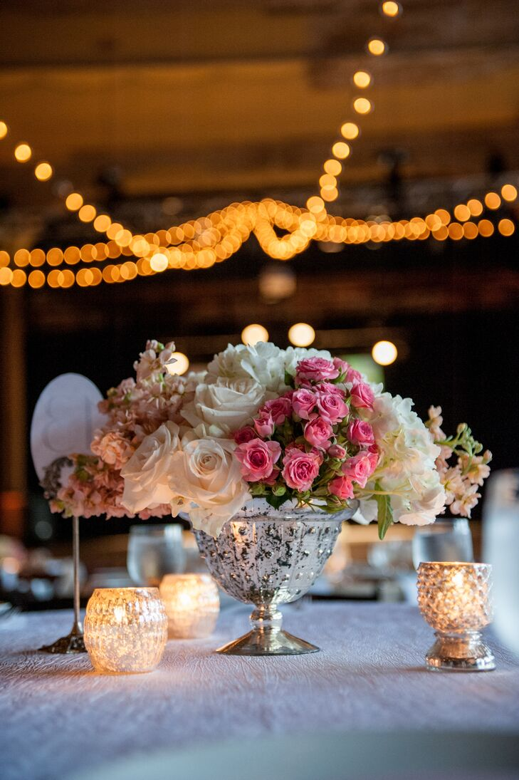 Centerpieces included flower arrangements of roses and hydrangeas in mercury vases surrounded by votive candles, adding to the romantic style.