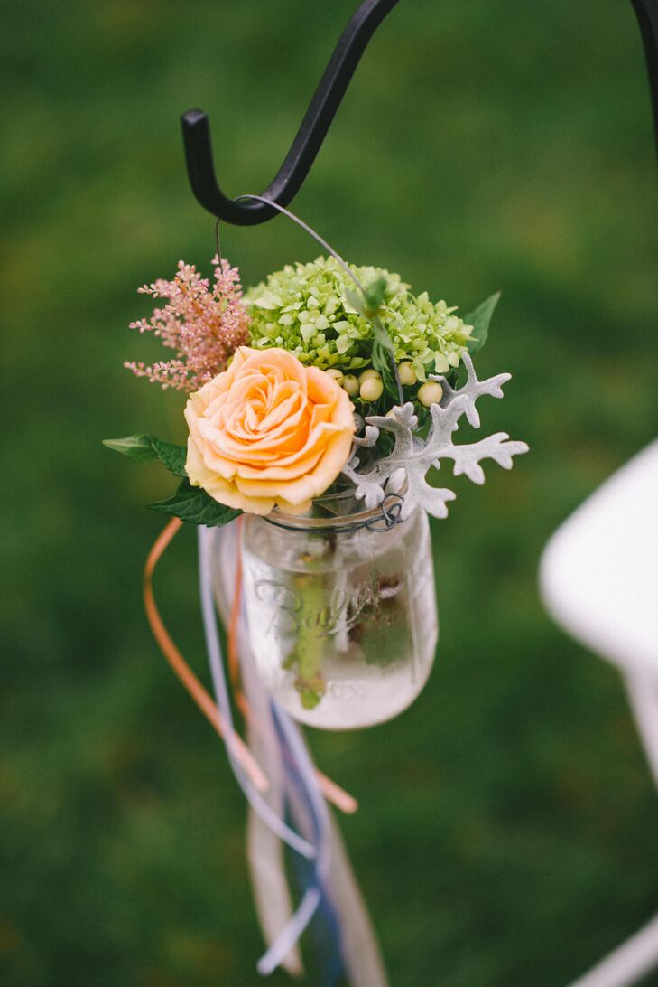 """We used a lot of mason jars to hold flowers and candles,"" says Emily. At the ceremony, jars were filled with peach roses, blush astilbe and silvery-green dusty miller leaves."