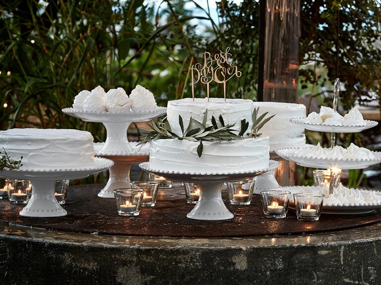 Outdoor woodland wedding dessert spread with cakes on white pearl-trim cake stands