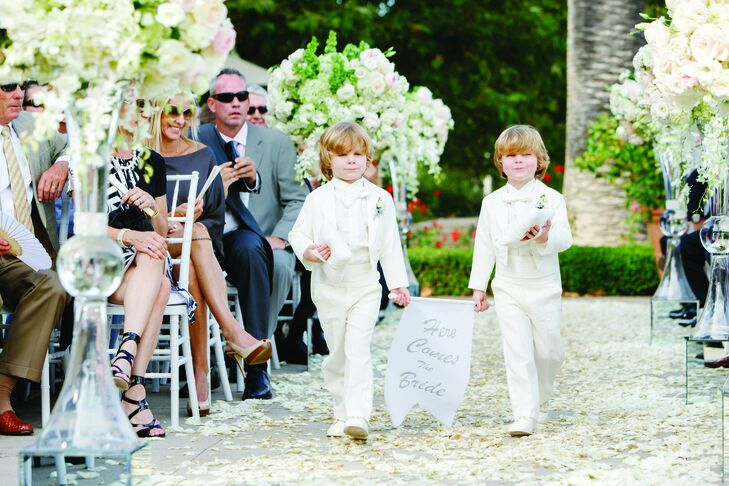 """Jessica and Matt had two particularly adorable ring bearers—Jessica's four-year-old identical-twin nephews, Dylan and Parker. The dapper little dudes wore matching white tuxes and carried a """"Here Comes the Bride"""" banner."""
