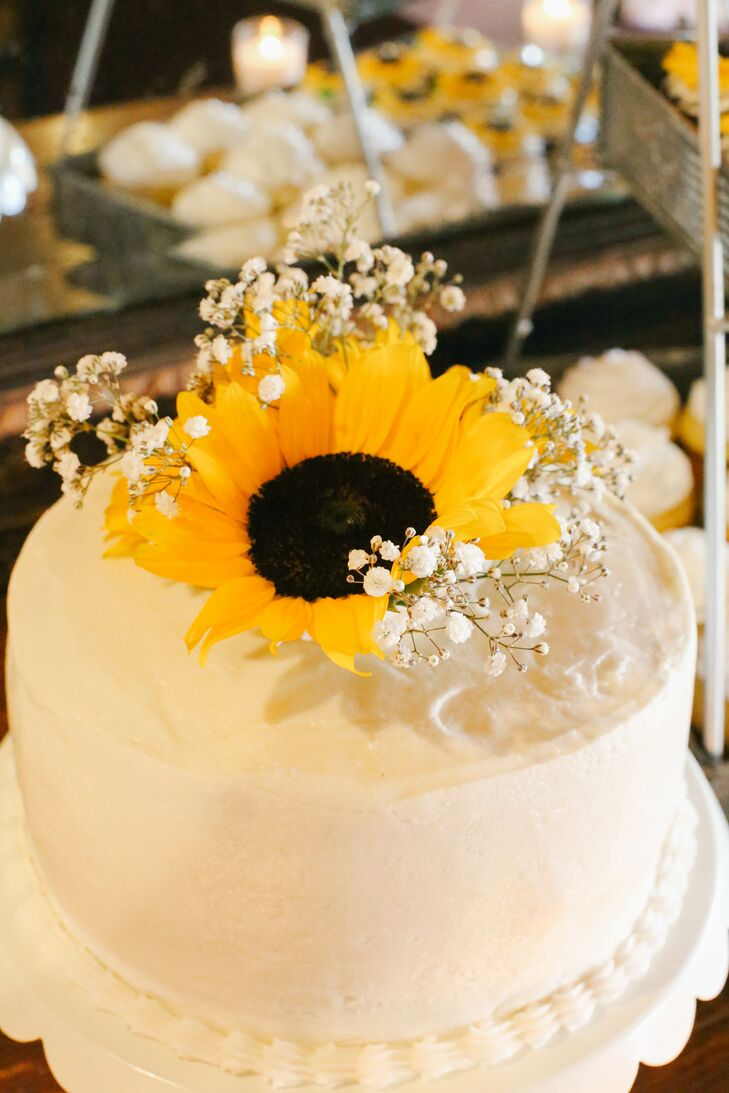 Stefanie Terrazas Bakery created a small single-tiered white wedding cake for Misty and Jake to cut at the reception, decorated with a single sunflower and baby's breath.rn