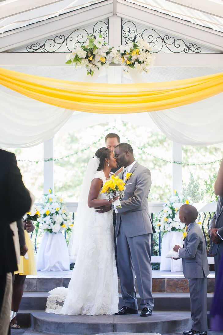 Jinitza and Brenton got married at the white wooden pavilion draped with white and canary yellow linens. The top and the sides of the structure had flower decorations that matched the linens, all matching one another to create a wonderful ceremony setting.