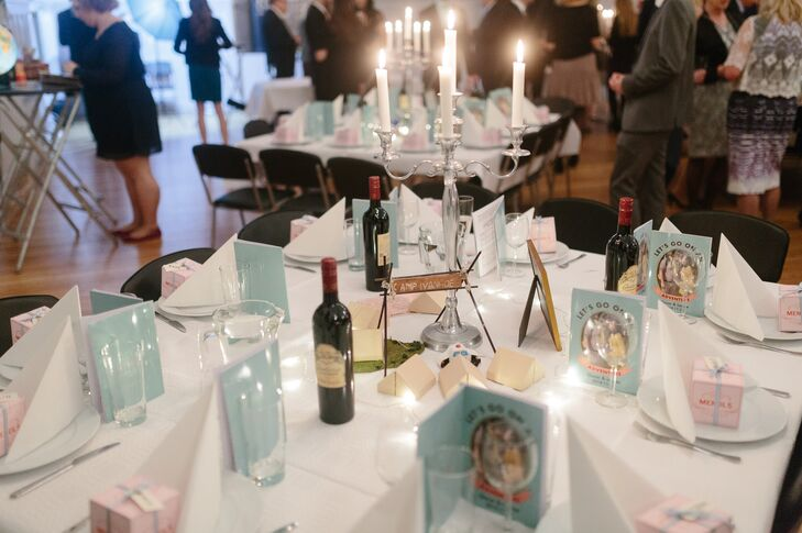 At the center of each dining table was a lit silver candelabra. One of the dining tables had a centerpiece that resembled Camp Ivanhoe from 'Moonrise Kingdom.' The reception programs and menus also reference 'Moonrise Kingdom.'