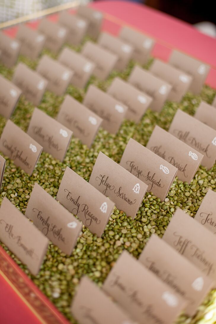 Light brown escort cards depicted names of guests, along with symbols that corresponded with dining tables. A box filled with green stones held the cards up, arranged neatly in rows for friends and family.