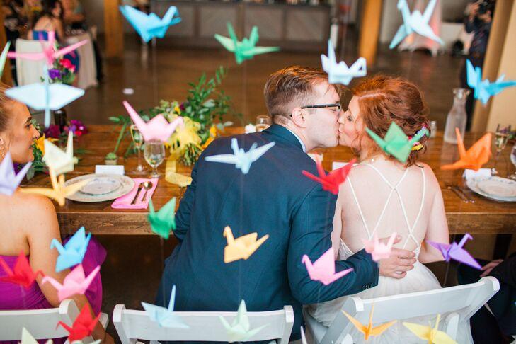 Couple Kissing Under Colorful Paper Crane Backdrop