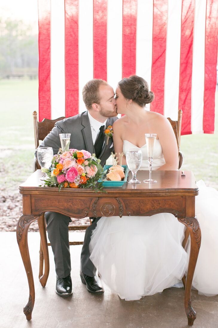 During the reception, Katie and Austin's sweetheart table was the picture of Americana. A large American flag was the backdrop for their vintage seating.