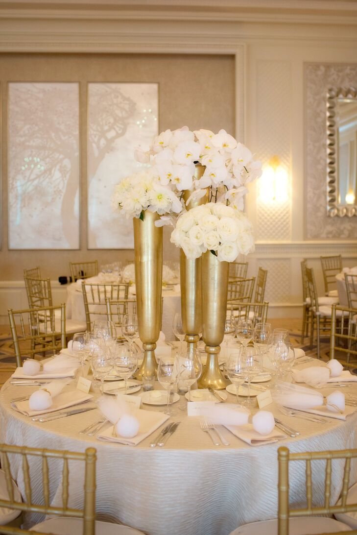 On the reception tables, all-white arrangements of peonies, orchids and roses sat atop tall gold vases.