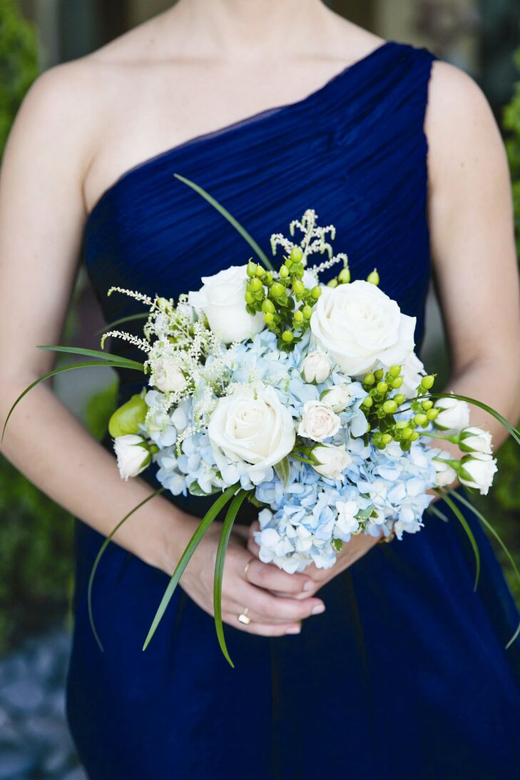 Each bridesmaid carried a loose, hand-tied bouquet filled with a mix of roses, hydrangeas, astilbe and hypernicum berries in shades of ivory, blue and bright green.