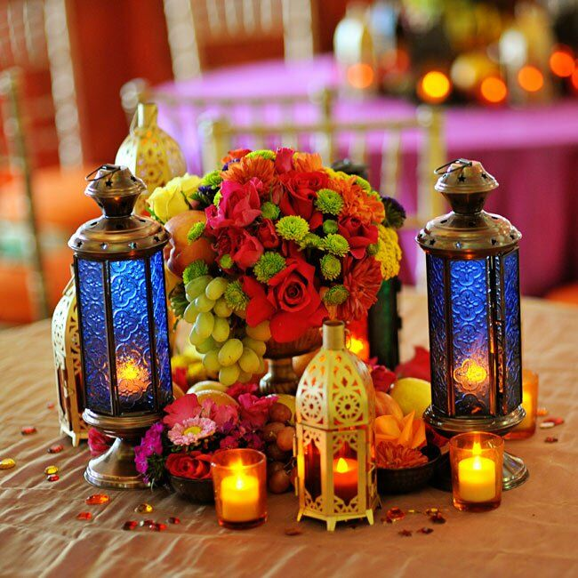 The tables were topped with arrangements of fruit and flowers in bold oranges, greens, pinks and yellows. Indian-style lanterns added warm candlelight to the tables.