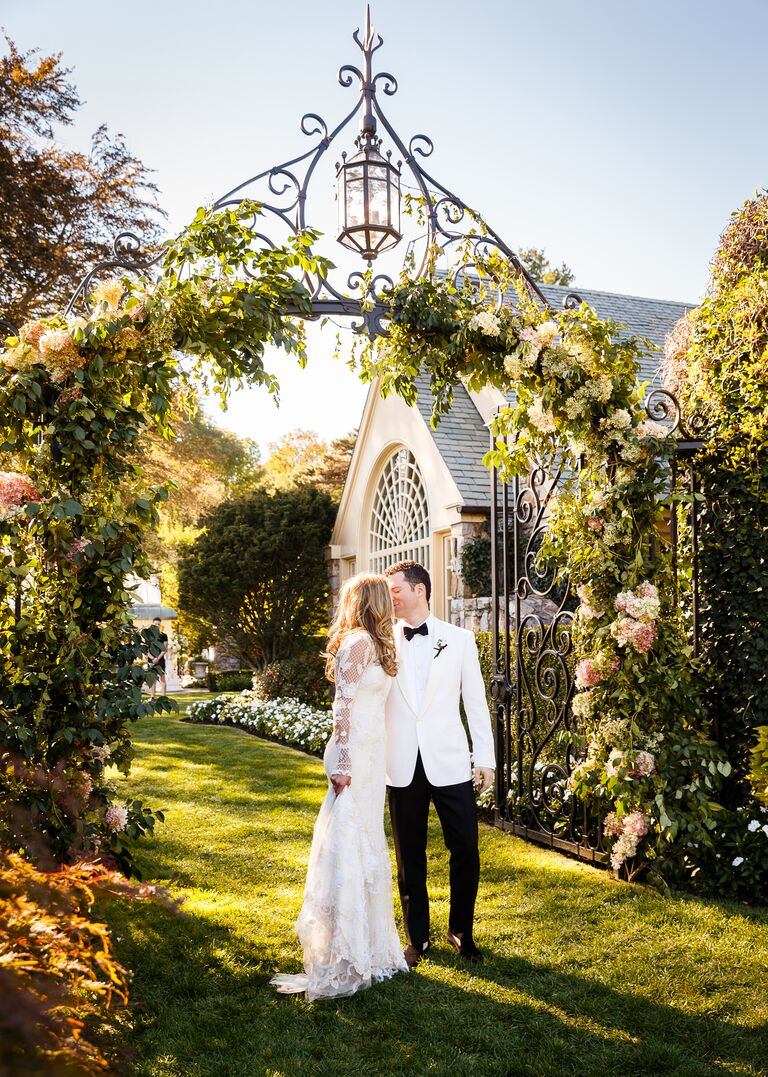 Bride and groom portrait under flower arbor