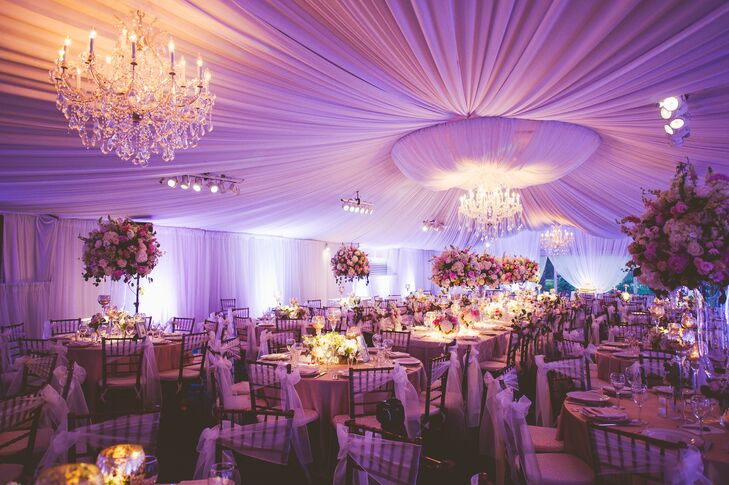 To carry the romantic feel through to the reception, the party tents were draped in white chiffon with crystal chandeliers hanging from the ceiling. The tablescapes featured the chosen flowers with champagne table linens and mercury glass candleholders to accent the pastel colors.