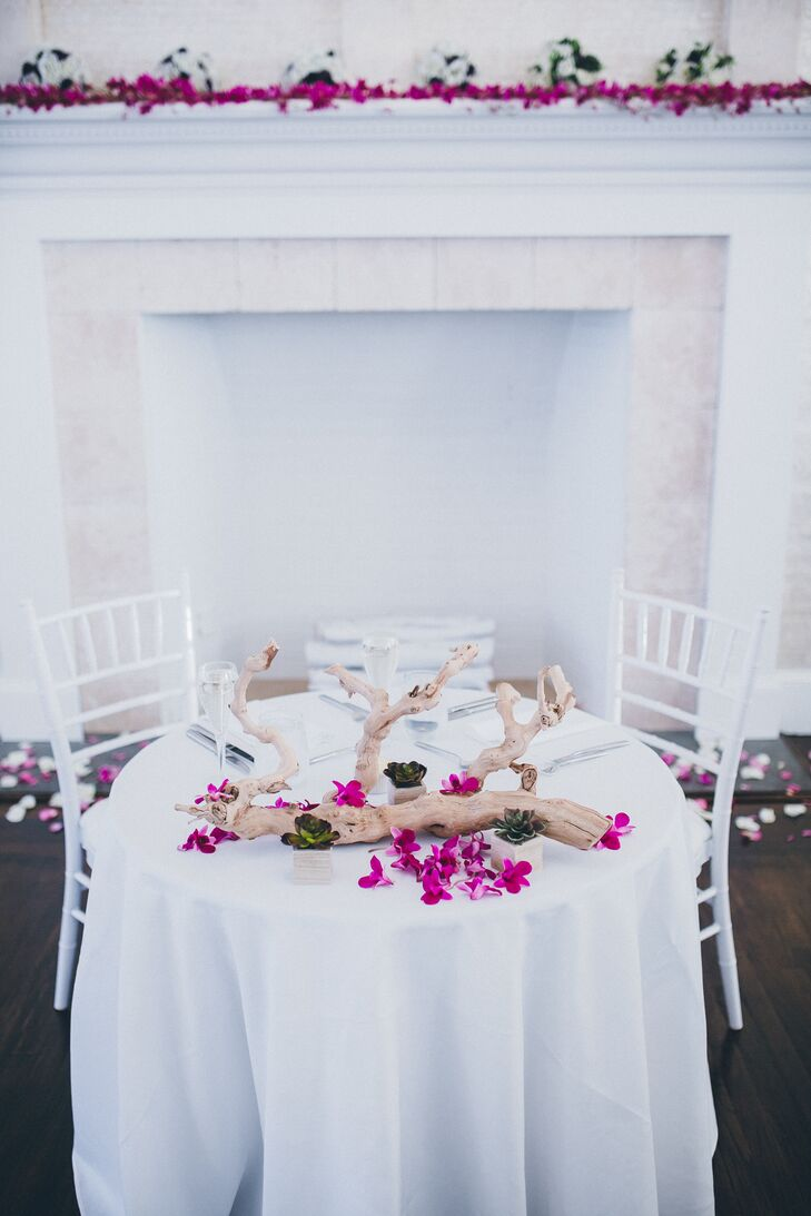 Simple arrangements of driftwood and fuchsia flowers decorated the couple's all-white sweetheart table.