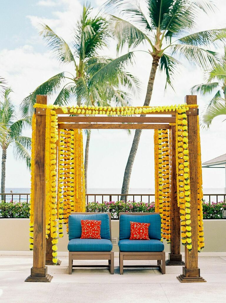 outdoor Indian wedding ceremony mandap decorated with yellow marigolds flowers garlands and bright blue upholstered chairs