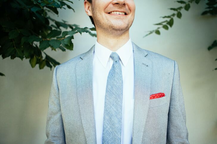 Brent's light blue suit put a casual spin on a classic look. The chambray suit, accented with a red polka-dotted pocket square, complemented the weddings rustic chic style and color palette.