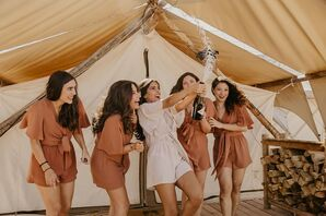 Getting Ready with Matching Robes and Champagne in Glamping Tent