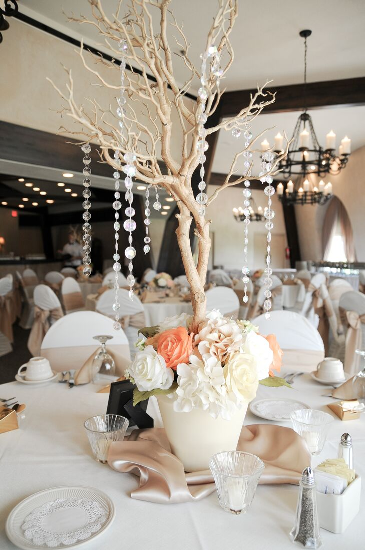 The reception centerpieces featured stunning manzanita trees with peach and pink roses, with lines of crystals draping from the branches, all set in ivory planters. Sitting on a blush linen, the centerpiece was surrounded by votive candles. We just love how high centerpieces fill a space.