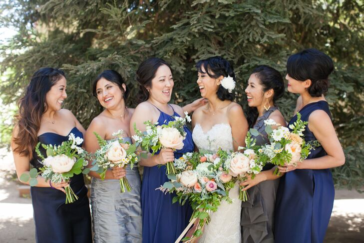 Naomi stood in the middle of her bridesmaids, who wore a variety of dresses in different shades of blue and gray. All the ladies stood with one another, holding their lush bouquets filled with a soft-colored wildflowers.
