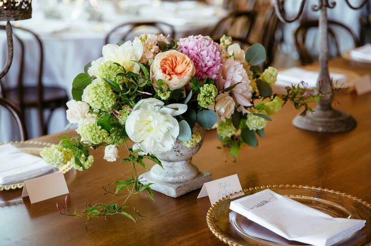 Kate and Jordan enlisted the help of the florists at Fleurs NYC to balance out the raw, industrial vibe of the Roundhouse's Waterfall Room. Together they dreamed up arrangements of full blooms like peonies, garden roses and dahlias in shades of peach, pink and ivory.