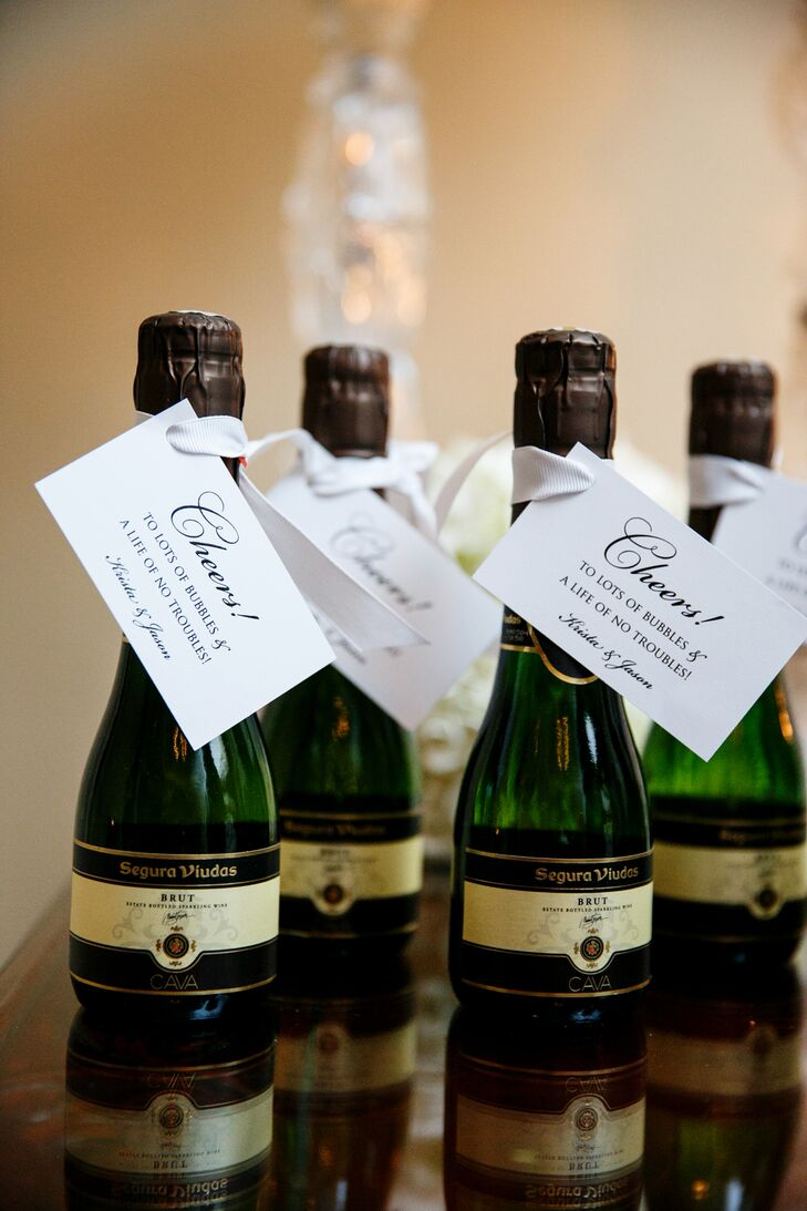 """True to form, Krista and Jason's capped off their 1920s-inspired reception with mini champagne bottle wedding favors for each of their guests. Each bottle came with a tag that said """"Cheers! A life of bubbles and no troubles."""""""