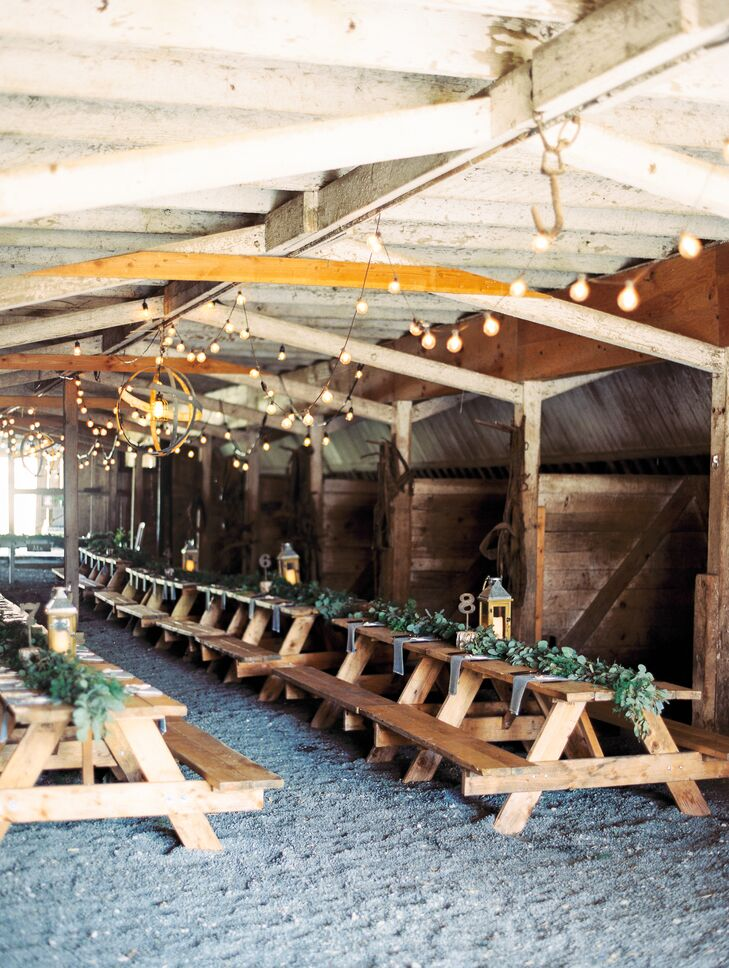 Inside the 19th-century barn, long wooden picnic tables were topped with simple eucalyptus garlands.
