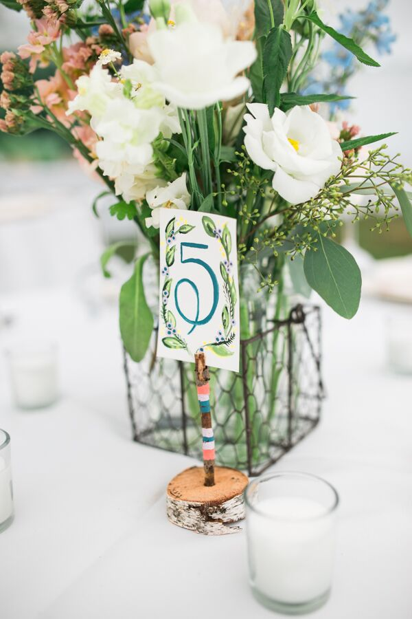 The couple opted for classic table numbers, but the design was anything but standard. Birch bases boasted color-blocked twigs and watercolor numbers decorated with painted garlands.