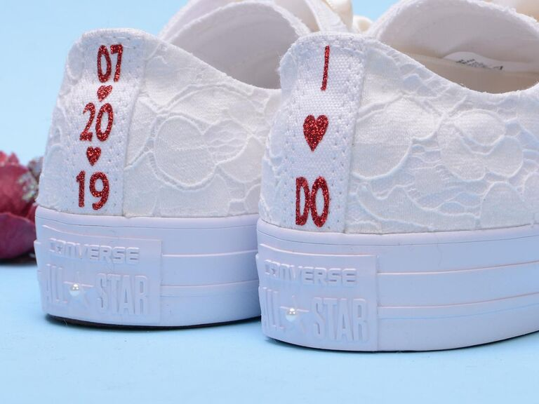 White lace low-top Converse wedding sneakers with personalization along the heel in red glitter