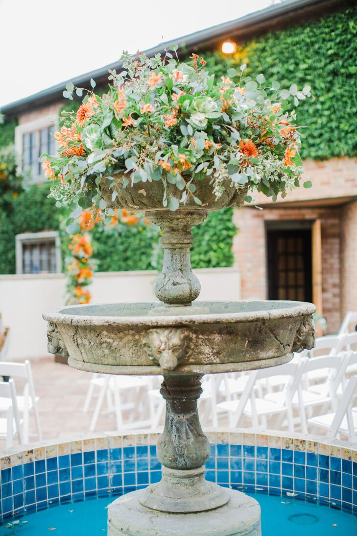 Overflowing greens and orange flowers in a natural, wildflower-inspired arrangement topped the fountain in the center of Alison and Pierce's courtyard ceremony setup at the Gallery in Houston, Texas.