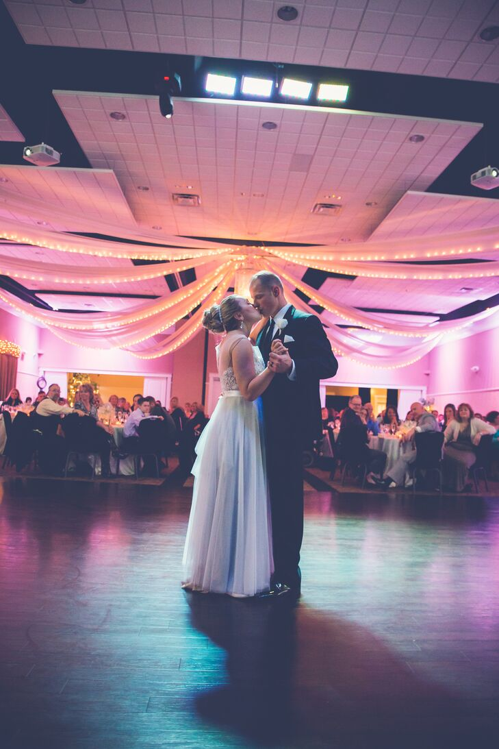 At the reception, Kyra and Wil shared their first dance together inside the dimly lit ballroom area, which was illuminated by the string lights hung from the ceiling. Guests watched from their dining tables dressed in ivory tablecloths that were set with silver dinnerware.