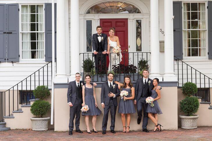 To compliment the groomsmen's charcoal gray tuxedos, the bridesmaids wore gray, A-line chiffon bridesmaid dresses that hit at the knee with black heels. Their bouquets were smaller versions of the bridal bouquet and included roses, ranunculuses and dusty miller. The wedding party is standing in front of the house where Beth's great-grandfather once lived.