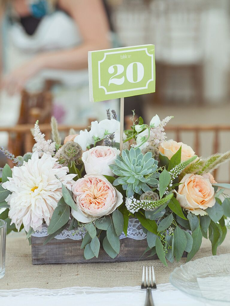 Rustic flower and succulent arrangement in a wooden planter for a wedding reception centerpiece