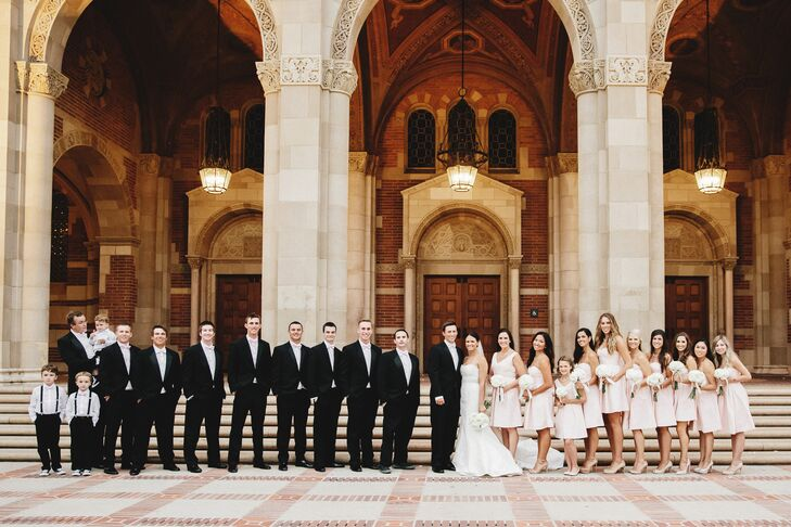 The married couple stood with their wedding party, who were dressed in black and blush attire. The groomsmen sported black tuxedos, and the bridesmaids wore blush short dresses.