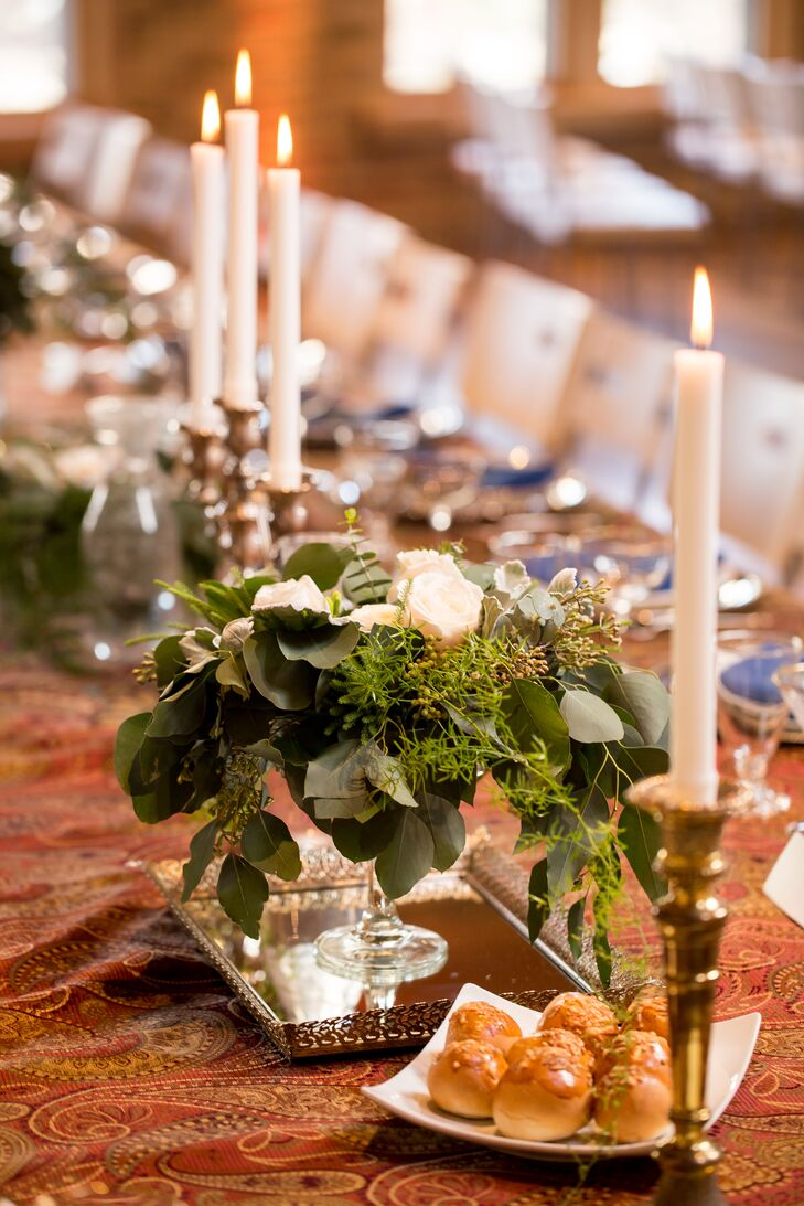 The long feasting table featured gold candlesticks with taper candles and low arrangements overflowing with moss and greenery.