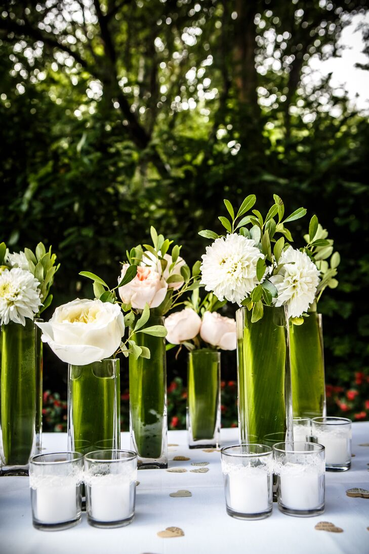 Jen and Eddie accented their wedding with candle light as well as white and blush dahlias, roses and garden roses in tall cylinder vases.