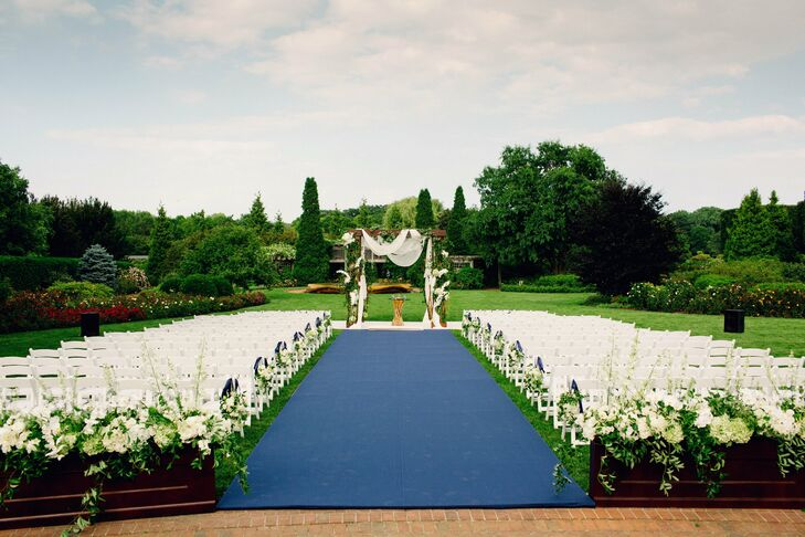 The couple's outdoor ceremony was held in the rose garden. Erin walked down a navy blue aisle runner for a bit of contrast to the lush green space.