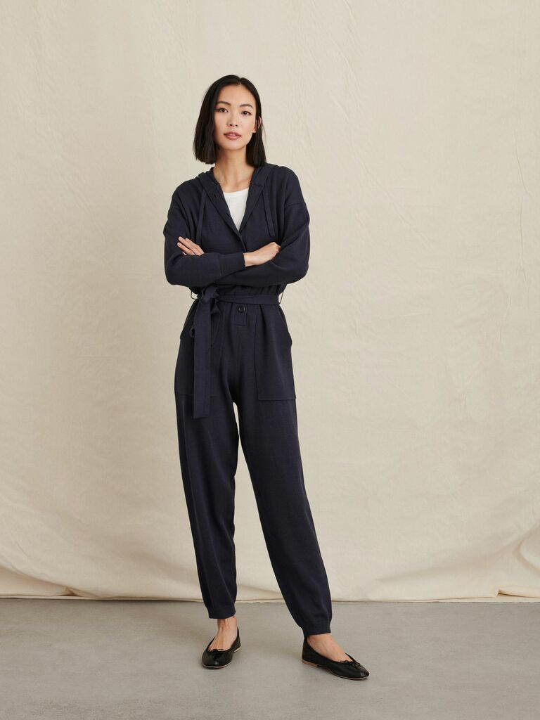 person wearing navy hooded sweater jumpsuit