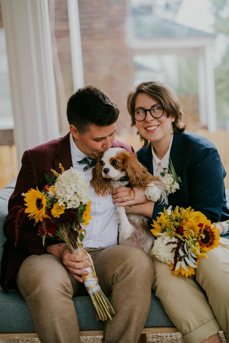 Couple posing with dog and sunflower bouquets