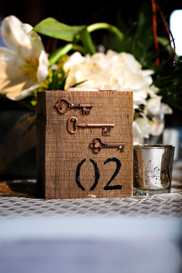 """""""On our first Valentine's Day, I gave Lee a special wood box that held the key to my heart,"""" says David. To represent this sweet part of their relationship, they used keys throughout the reception decor, including half of the table numbers. Each wooden accent was decorated with a set of copper keys along the front."""