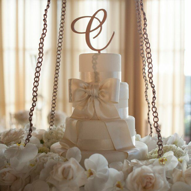 The wedding cake was kept simple with each layer wrapped in ivory ribbon and finished with a fondant bow. The majority of the cake was just for show, except for the very top layer, which the couple used for the cake cutting. For the rest of their 270 guests, the couple served two sheet cakes, a red velvet sponge cake with cream cheese filling, and white sponge cake with fresh strawberries and vanilla bavarian cream filling.