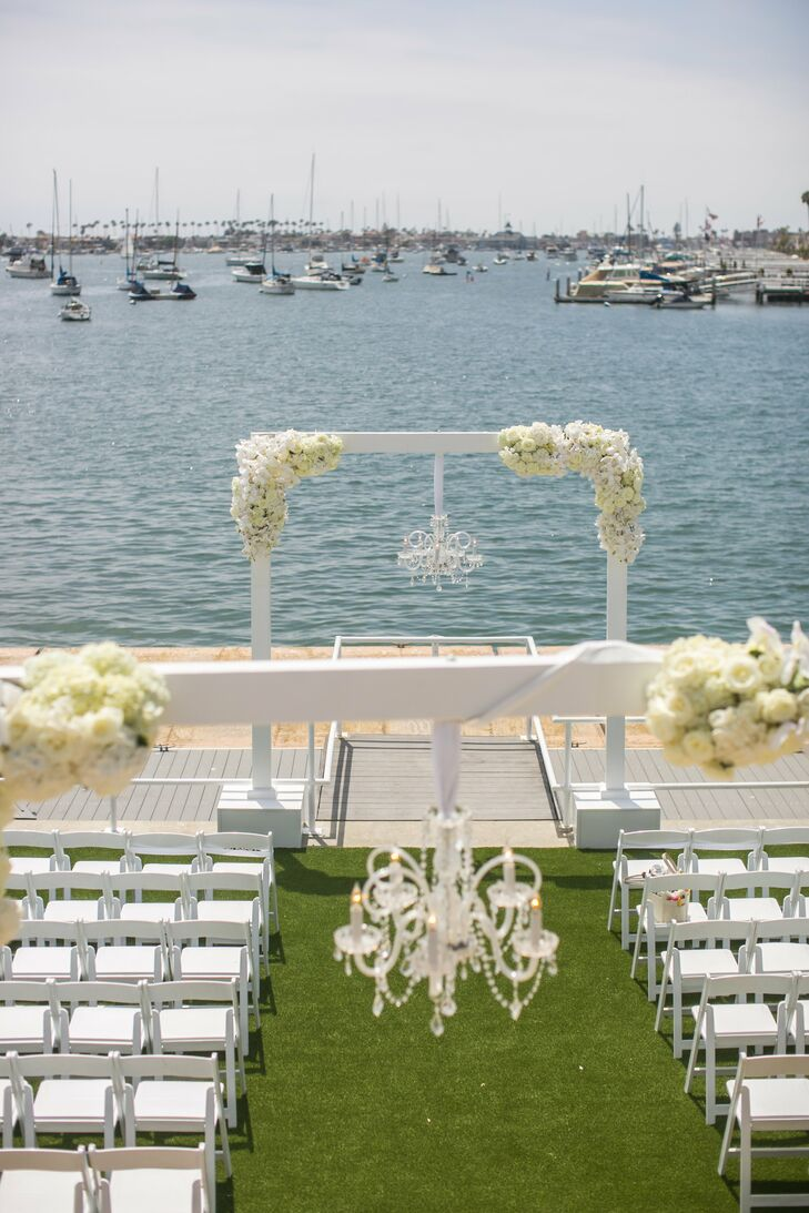 At the outdoor ceremony at Balboa Yacht Club in Corona del Mar, California, a sleek, modern wedding arch was adorned with two lush garlands of white blossoms.