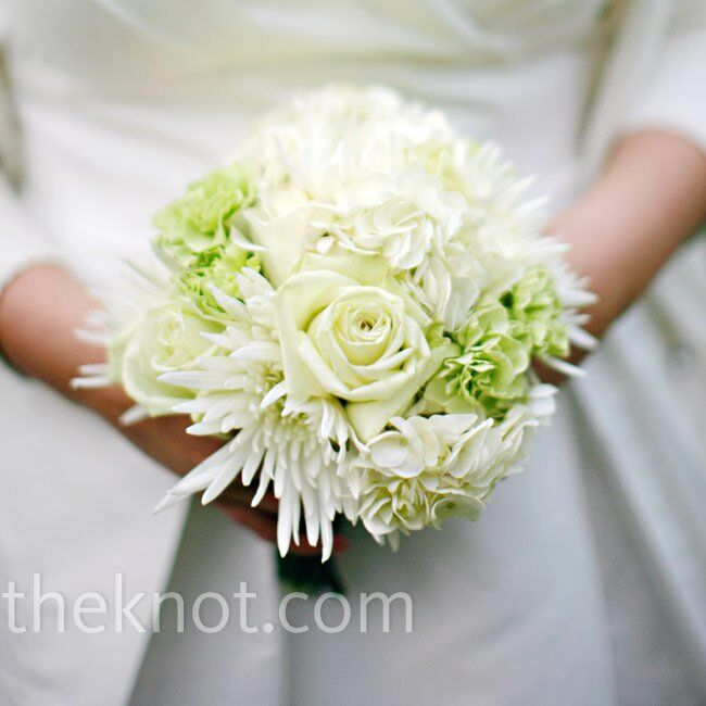 """Megan carried an all-white bouquet of roses, spider mums, hydrangeas, and green carnations she purchased with her sister. """"Making our own arrangements was easy and a great way to save money and spend time together before the big day,"""" says the bride."""