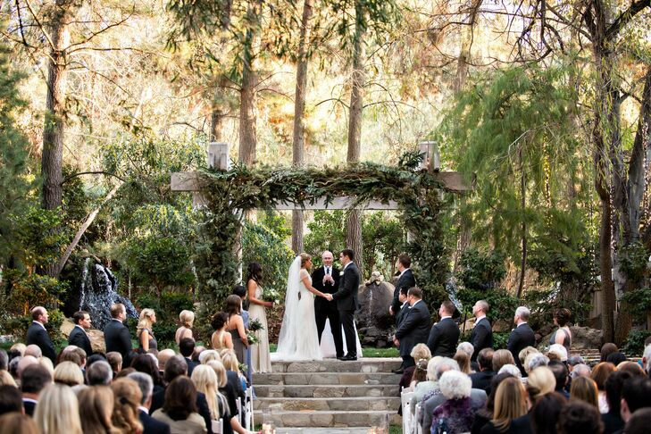 The ceremony took place outdoors in a wooded clearing. The couple stood under a simple wooden arch decorated with a lush fir and pine garland that complemented the rustic locale.