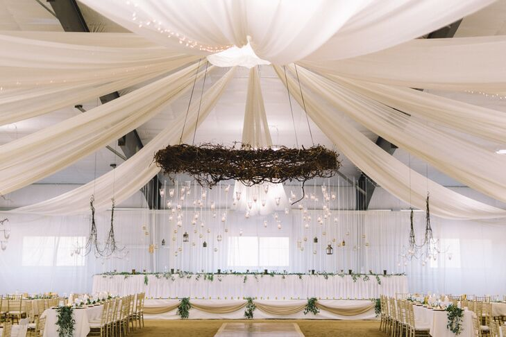 Oriana's dad built the head table stage, with a 10-foot grapevine wreath and 100 candles hanging from the center.
