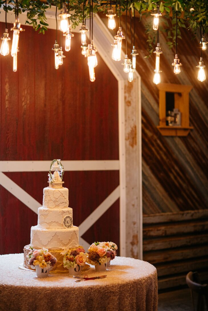 A hanging installation of greenery and Edison bulbs illuminated the cake.