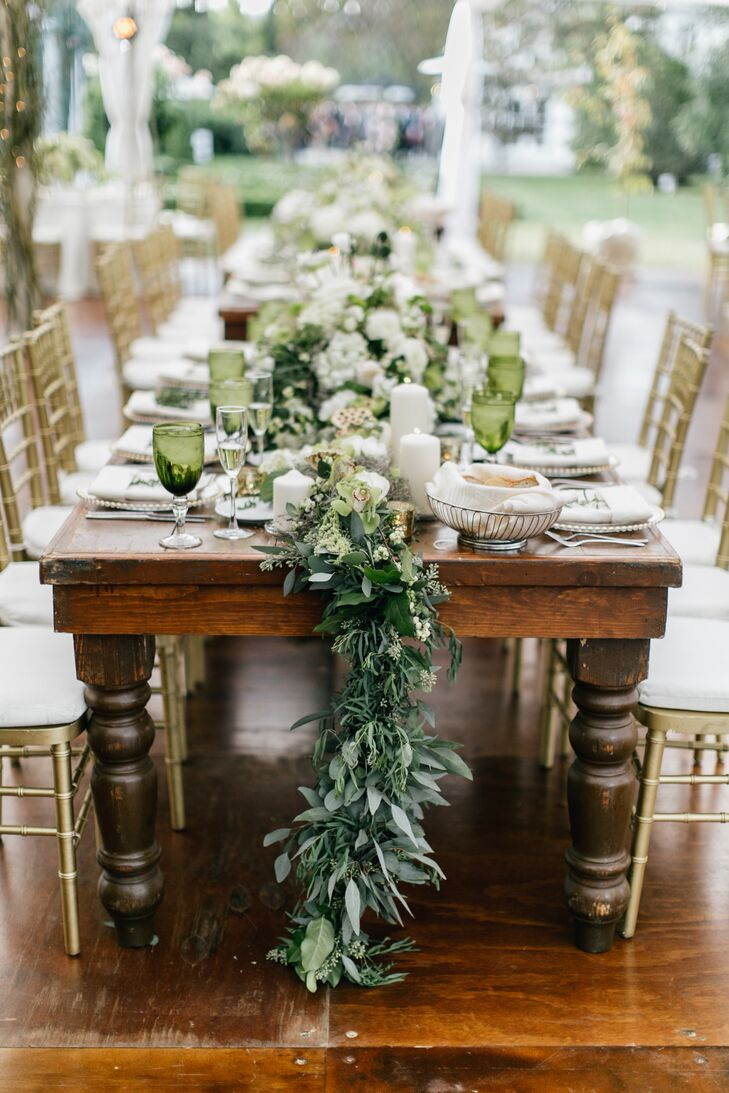 Eucalyptus garland runners accented with hydrangeas and lots of candles lined the farm tables. Green glasses and gold chairs added dimension to the table settings.